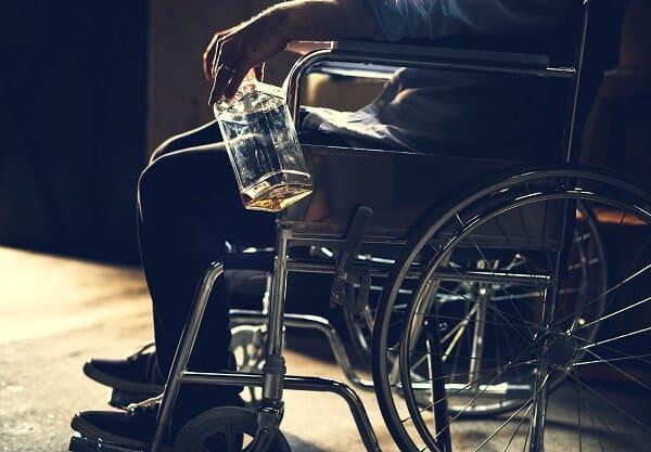 alkoholik siedzący na wózku inwalidzkim