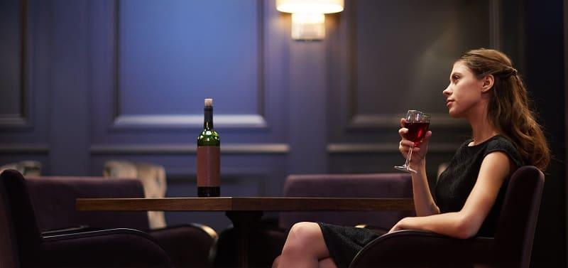 kobieta pijąca w samotności wino